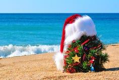 Καπέλο χριστουγεννιάτικων δέντρων και santa στην άμμο στην παραλία Στοκ Φωτογραφία