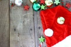 Καπέλο Santa και διακόσμηση Χριστουγέννων στο ξύλινο υπόβαθρο με το διάστημα αντιγράφων Στοκ Εικόνα
