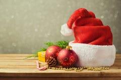 Καπέλο Santa με τις διακοσμήσεις Χριστουγέννων στον ξύλινο πίνακα πέρα από το υπόβαθρο θαμπάδων Στοκ Εικόνες