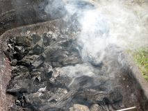 Καπνίζοντας καίγοντας ξυλάνθρακας στη σχάρα Στοκ Εικόνες