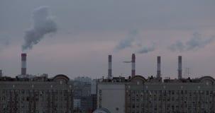Καπνίζοντας καπνοδόχοι, στέγες πόλεων και ένα πετώντας αεροπλάνο απόθεμα βίντεο