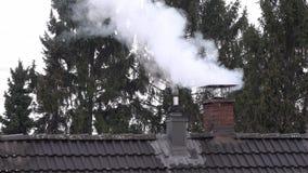 Καπνίζοντας καπνοδόχος και σωλήνας στην κορυφή ενός σπιτιού με το τρεμούλιασμα θερμότητας απόθεμα βίντεο