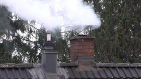 Καπνίζοντας καπνοδόχος και σωλήνας στην κορυφή ενός σπιτιού με το τρεμούλιασμα θερμότητας φιλμ μικρού μήκους