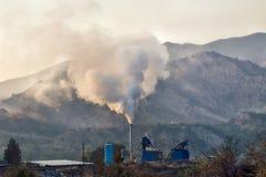 Καπνίζοντας σωλήνας ενός μικρού εργοστασίου ασφάλτου που βρίσκεται στα βουνά Στοκ Εικόνες