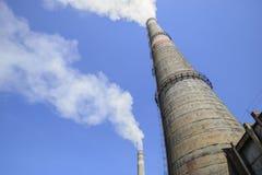 Καπνίζοντας σωλήνες των εγκαταστάσεων παραγωγής ενέργειας ενάντια στο μπλε ουρανό Στοκ Φωτογραφία
