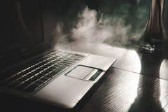 Καπνίζοντας hookah λειτουργώντας στο lap-top στο σπίτι, το σκοτεινό θέμα, κλείνει επάνω, ελαφριές γραμμές ήλιων στοκ εικόνες