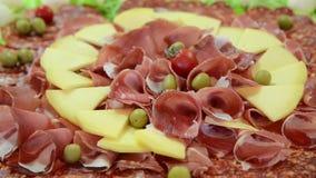Καπνισμένα κρέας και τυρί σε ένα πιάτο Τακτοποιημένο ξηρό κρέας στο εστιατόριο ορεκτικός Θεραπευμένη πιατέλα κρέατος φιλμ μικρού μήκους