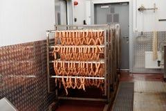 Καπνισμένα λουκάνικα στο εργοστάσιο επεξεργασίας τροφίμων στοκ φωτογραφίες