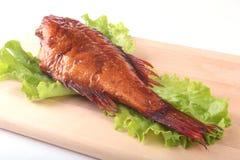 Καπνισμένα ψάρια και λεμόνι στα πράσινα φύλλα μαρουλιού στον ξύλινο τέμνοντα πίνακα που απομονώνεται στο άσπρο υπόβαθρο Στοκ φωτογραφία με δικαίωμα ελεύθερης χρήσης