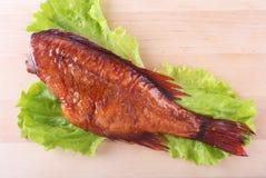Καπνισμένα ψάρια και λεμόνι στα πράσινα φύλλα μαρουλιού στον ξύλινο τέμνοντα πίνακα που απομονώνεται στο άσπρο υπόβαθρο Στοκ εικόνα με δικαίωμα ελεύθερης χρήσης