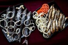 Καπνισμένα ψάρια ποταμών που εξυπηρετούνται με τις ντομάτες και τα κρεμμύδια Η άποψη από Στοκ Εικόνες
