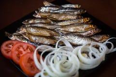Καπνισμένα ψάρια ποταμών που εξυπηρετούνται με τις ντομάτες και τα κρεμμύδια Η άποψη από Στοκ Εικόνα