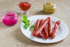 Καπνισμένες λουκάνικα, μουστάρδα, χρένο και σάλτσα σε ένα πιάτο Στοκ Εικόνες