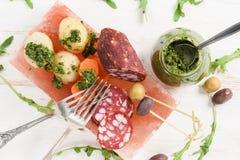 Καπνισμένες σαλάμι, πατάτες και ελιές με την πράσινη σάλτσα chimichurri Στοκ Φωτογραφία