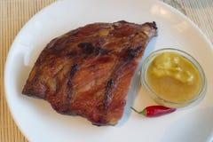 Καπνισμένες ψημένες πλευρά χοιρινού κρέατος και σάλτσα του μελιού με την πιπερόριζα και τη μουστάρδα στοκ φωτογραφία