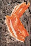 Καπνισμένες Prosciutto φέτες ζαμπόν χοιρινού κρέατος στην πολύ παλαιά ξύλινη επιφάνεια Στοκ φωτογραφία με δικαίωμα ελεύθερης χρήσης