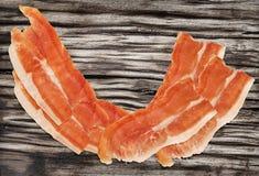 Καπνισμένες Prosciutto φέτες ζαμπόν χοιρινού κρέατος στην πολύ παλαιά ξύλινη επιφάνεια Στοκ εικόνες με δικαίωμα ελεύθερης χρήσης