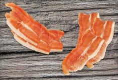 Καπνισμένες Prosciutto φέτες ζαμπόν χοιρινού κρέατος στο πολύ παλαιό ξύλο Στοκ Φωτογραφίες