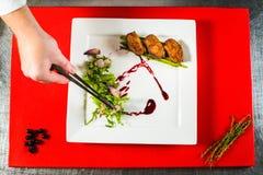 καπνισμένη λωρίδα στηθών παπιών στο άσπρο πιάτο στον κόκκινο μαγειρικό πίνακα Στοκ φωτογραφία με δικαίωμα ελεύθερης χρήσης
