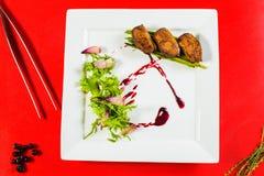καπνισμένη λωρίδα στηθών παπιών στο άσπρο πιάτο στον κόκκινο μαγειρικό πίνακα Στοκ Φωτογραφίες
