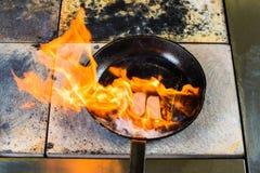 καπνισμένη λωρίδα στηθών παπιών στο μαγειρεύοντας τηγάνι στον κόκκινο μαγειρικό πίνακα Στοκ Εικόνες