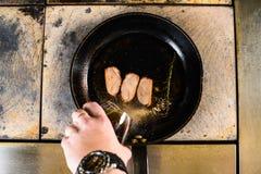 καπνισμένη λωρίδα στηθών παπιών στο μαγειρεύοντας τηγάνι στον κόκκινο μαγειρικό πίνακα Στοκ εικόνα με δικαίωμα ελεύθερης χρήσης