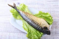 Καπνισμένος mackerele και λεμόνι στα πράσινα φύλλα μαρουλιού στον ξύλινο τέμνοντα πίνακα που απομονώνεται στο άσπρο υπόβαθρο Στοκ Φωτογραφία