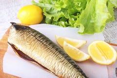 Καπνισμένος mackerele και λεμόνι στα πράσινα φύλλα μαρουλιού στον ξύλινο τέμνοντα πίνακα που απομονώνεται στο άσπρο υπόβαθρο Στοκ Εικόνες