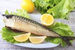 Καπνισμένος mackerele και λεμόνι στα πράσινα φύλλα μαρουλιού στον ξύλινο τέμνοντα πίνακα που απομονώνεται στο άσπρο υπόβαθρο Στοκ φωτογραφίες με δικαίωμα ελεύθερης χρήσης