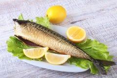 Καπνισμένος mackerele και λεμόνι στα πράσινα φύλλα μαρουλιού στον ξύλινο τέμνοντα πίνακα που απομονώνεται στο άσπρο υπόβαθρο Στοκ εικόνες με δικαίωμα ελεύθερης χρήσης