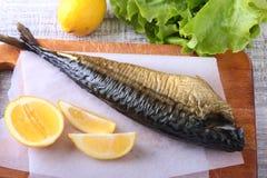 Καπνισμένος mackerele και λεμόνι στα πράσινα φύλλα μαρουλιού στον ξύλινο τέμνοντα πίνακα στο άσπρο υπόβαθρο Στοκ φωτογραφίες με δικαίωμα ελεύθερης χρήσης