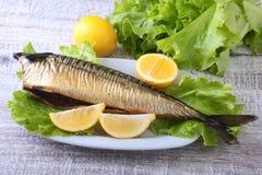 Καπνισμένος mackerele και λεμόνι στα πράσινα φύλλα μαρουλιού στον ξύλινο τέμνοντα πίνακα στο άσπρο υπόβαθρο Στοκ Φωτογραφία