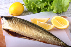 Καπνισμένος mackerele και λεμόνι στα πράσινα φύλλα μαρουλιού στον ξύλινο τέμνοντα πίνακα που απομονώνεται στο άσπρο υπόβαθρο Στοκ φωτογραφία με δικαίωμα ελεύθερης χρήσης