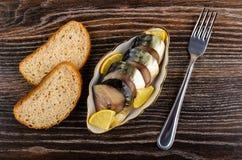 Καπνισμένο σκουμπρί με το λεμόνι στο κύπελλο, ψωμί, δίκρανο στον πίνακα Τοπ όψη στοκ φωτογραφία