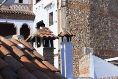 Καπνοδόχοι, στέγες, μπλε και κόκκινα χρώματα στο μαροκινό χωριό Στοκ εικόνα με δικαίωμα ελεύθερης χρήσης