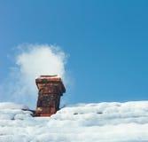 Καπνός από μια καπνοδόχο τούβλου σε ένα χιονώδες σπίτι στεγών Στοκ Φωτογραφία