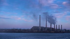 Καπνός από τους σωλήνες του σταθμού εγκαταστάσεων παραγωγής ενέργειας στις όχθεις ενός ποταμού απόθεμα βίντεο