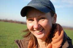 ΚΑΠ που χαμογελά υπαίθρια τη γυναίκα Στοκ Φωτογραφία