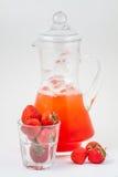 Καράφα γυαλιού με το χυμό και τον πάγο φραουλών Στοκ Φωτογραφία