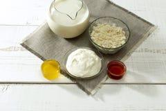 Καράφα του γάλακτος, ξινή κρέμα, τυρί εξοχικών σπιτιών στα φλυτζάνια στοκ φωτογραφία