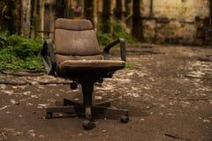 Καρέκλα βραχιόνων γραφείων στην εγκαταλειμμένη αίθουσα βιομηχανίας στοκ εικόνες