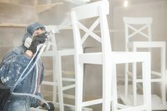 Καρέκλα ζωγραφικής ατόμων στο άσπρο χρώμα στην αναπνευστική μάσκα Εφαρμογή της φλόγας - καθυστερών που εξασφαλίζει πυροπροστασία Στοκ φωτογραφία με δικαίωμα ελεύθερης χρήσης