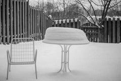 Καρέκλα patio κατωφλιών και χιονισμένος πίνακας σε γραπτό στοκ φωτογραφία με δικαίωμα ελεύθερης χρήσης
