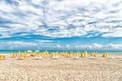 Καρέκλες και ομπρέλες παραλιών στο νεφελώδη ουρανό στο Μαϊάμι, ΗΠΑ Παραλία θάλασσας με την άσπρη άμμο και μπλε νερό την ηλιόλουστ Στοκ εικόνες με δικαίωμα ελεύθερης χρήσης