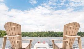 Καρέκλες Muskoka που αγνοούν τη λίμνη με ένα κύπελλο των κερασιών και ένα ποτήρι της σαμπάνιας μέσα - μεταξύ στοκ εικόνα