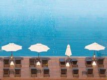 Καρέκλες παραλιών και δευτερεύουσα πισίνα ομπρελών στοκ εικόνες