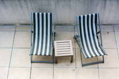 Καρέκλες παραλιών και μικρή επιτραπέζια πλησίον πισίνα Στοκ Φωτογραφία