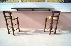 Καρέκλες πινάκων και raffia Στοκ Φωτογραφίες