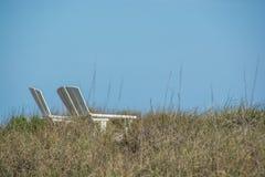 Καρέκλες σαλονιών στους αμμόλοφους παραλιών Στοκ εικόνες με δικαίωμα ελεύθερης χρήσης