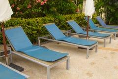 Καρέκλες χαλάρωσης εκτός από της πισίνας μέσα ξενοδοχείο Στοκ Εικόνες